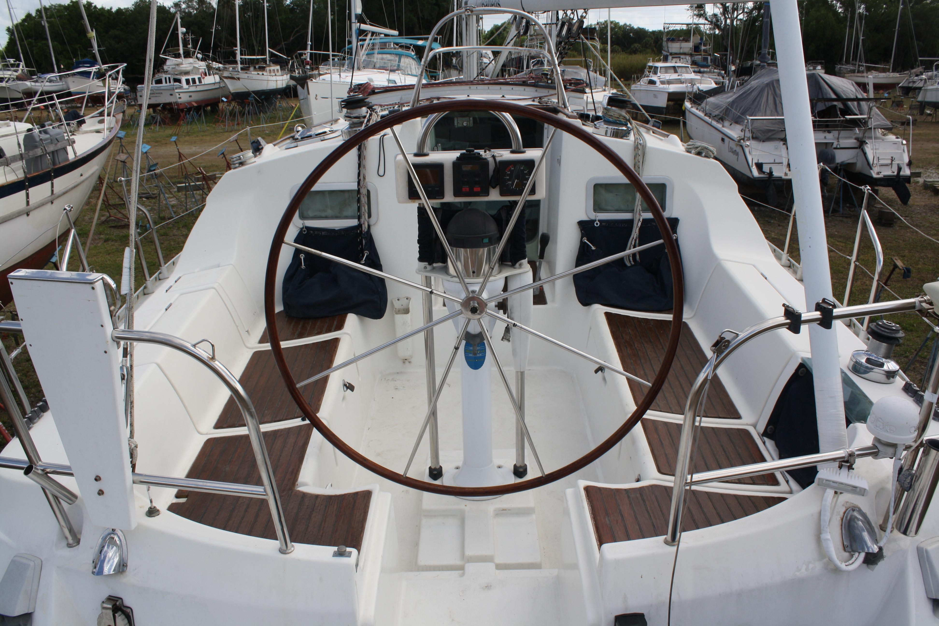 Beautiful Mahogany wheel and teak seats in a large comfortable cockpit