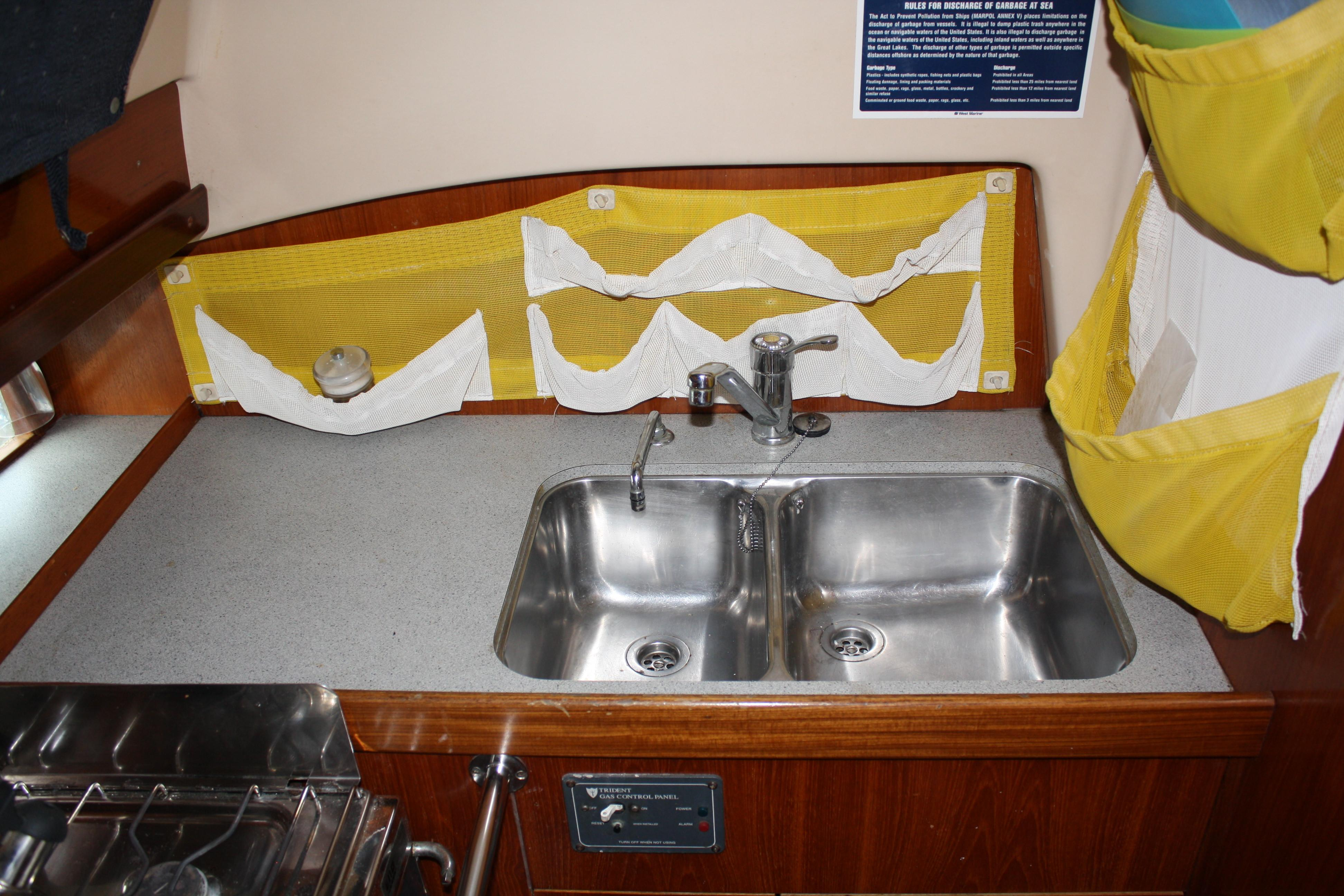 Large double bowl stainless steel sink at aft facing portion of the galley. The owners added many functional organizers in the galley area.
