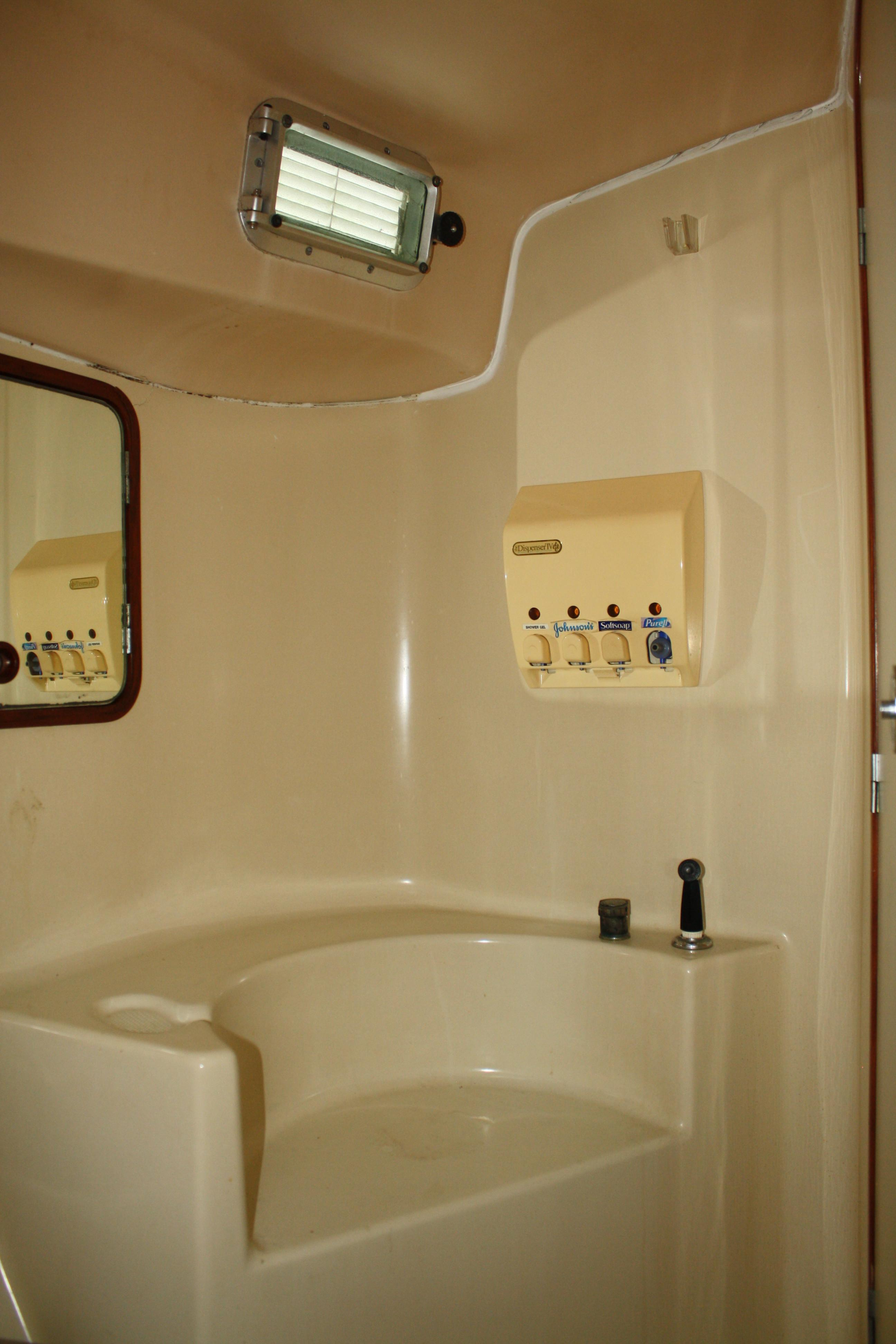 The shower portion of the single head has a large seat and is well away from the sink, head, and storage area. The gelcoat is white not cream.