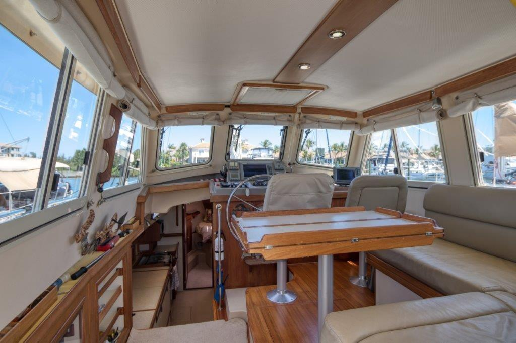 Spacious pilot house with settee, dining table and internal helm